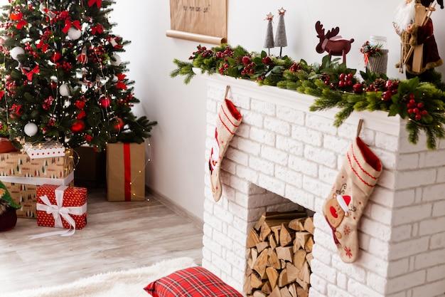 A árvore de natal fica perto de presentes Foto Premium