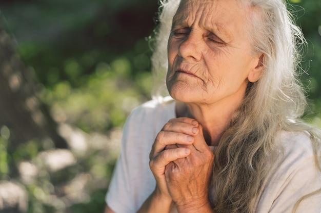 A avó de cabelos grisalhos está orando ao ar livre. Foto Premium