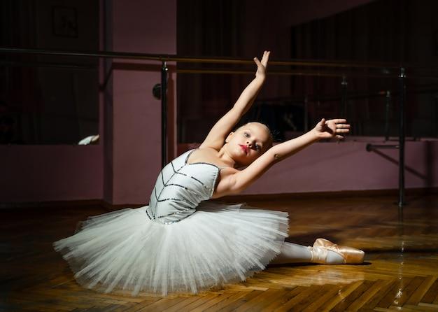 A bailarina bonita com coque coletou o cabelo usando vestido branco e sapatilhas com as mãos levantadas, sentado no chão de madeira. Foto Premium
