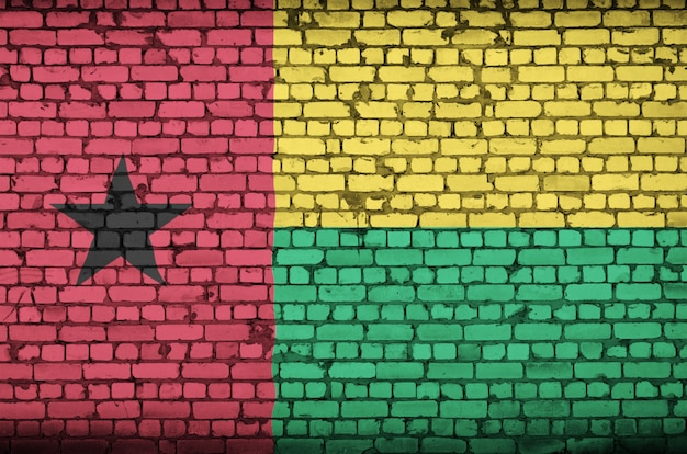 A bandeira da guiné-bissau é pintada em uma parede de tijolos antigos Foto Premium