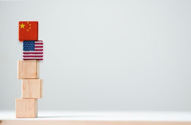 A bandeira dos eua e a bandeira de china imprimem a tela no cúbico de madeira. é símbolo da barreira do imposto da guerra do comércio da tarifa entre os estados unidos da américa e a china Foto Premium