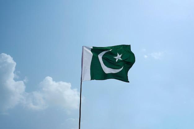 A bandeira nacional do paquistão voando no céu azul com nuvens Foto Premium