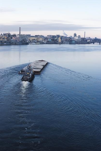 A barcaça flutuando no rio dnieper. paisagem da cidade de kiev no fundo. 17.11.2018 Foto Premium