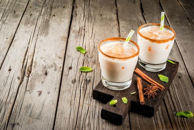 A bebida tradicional indiana é chá gelado ou chai masala, com cubos de gelo de folhas de chai, leite e hortelã. com canudos listrados, sobre uma tábua de madeira. em uma velha mesa de madeira rústica. copie o espaço Foto Premium