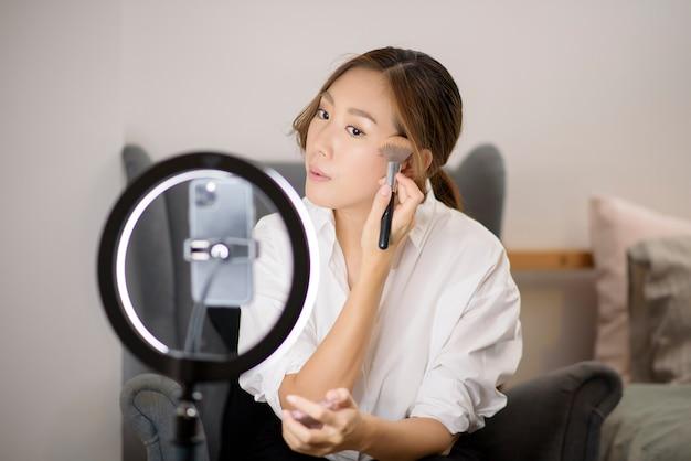 A bela blogueira de maquiagem está transmitindo ao vivo como usar maquiagem facial em sua casa Foto Premium