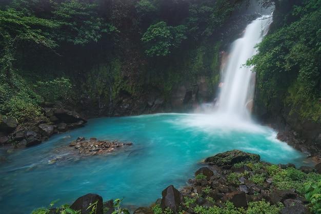A bela celeste colorido águas sedosas da cachoeira río celeste na costa rica Foto Premium