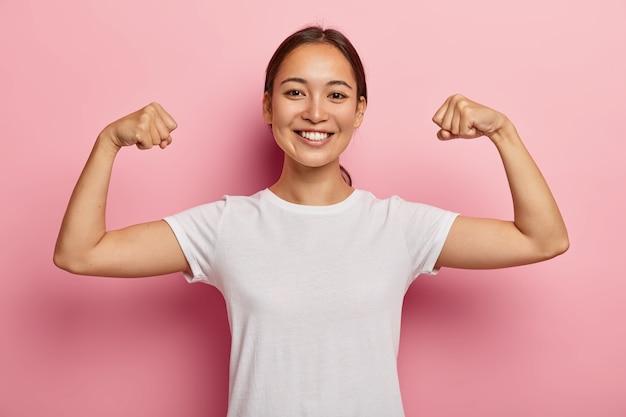 A bela modelo coreana se mantém em forma e saudável, levanta as mãos e mostra os músculos, sente-se orgulhosa de suas conquistas na academia, sorri amplamente, vestida com roupas casuais brancas, poses em ambiente fechado mostram verdadeiro poder Foto gratuita