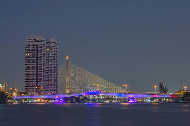 A beleza das luzes coloridas na ponte pinklao e carros dirigindo à noite no rio chao phraya Foto Premium