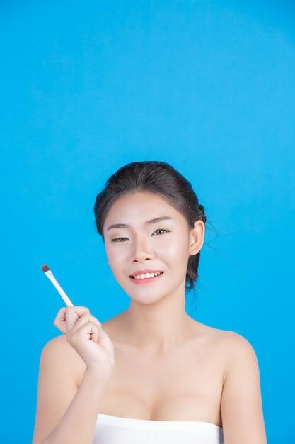 A beleza das mulheres com imagens perfeitas de saúde da pele tocando em seu rosto e sorrindo como um spa para cuidar de sua pele azul Foto gratuita