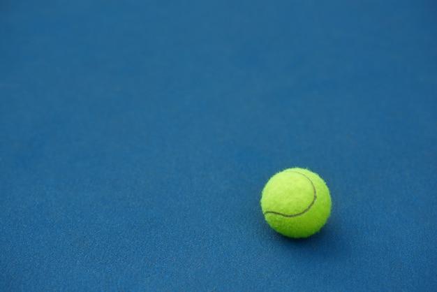 A bola de tênis brilhante amarela está mentindo sobre no fundo azul do tapete. feito para jogar tênis. quadra de tênis azul. Foto gratuita