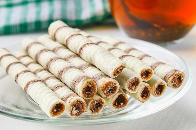 A bolacha listrada rola, petisco delicioso do chocolate na tabela de madeira branca. Foto Premium