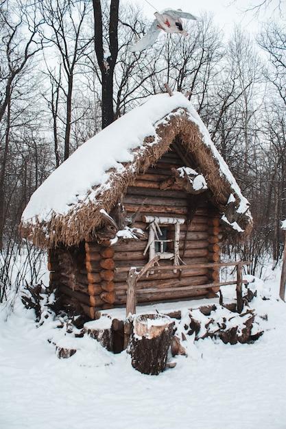 A cabana fica na floresta na neve do inverno Foto Premium
