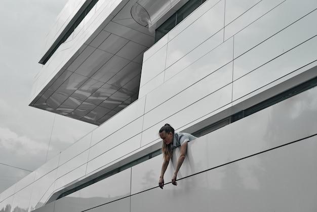 A cabeça e os ombros da garota estão contra o fundo do prédio, seus braços pendurados sobre a cerca. geometria em construção. Foto Premium