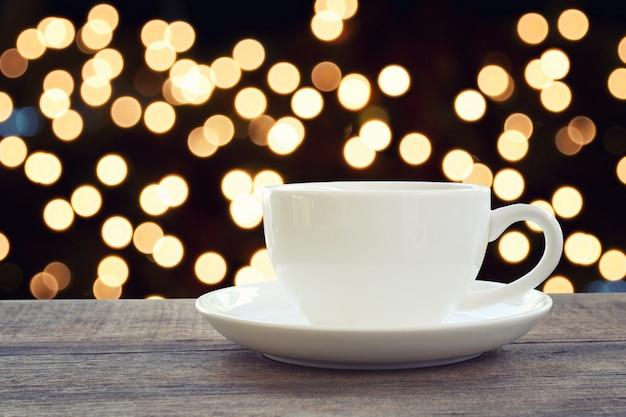 A caneca de café branco no assoalho de madeira marrom e tem o fundo claro do bokeh. Foto Premium