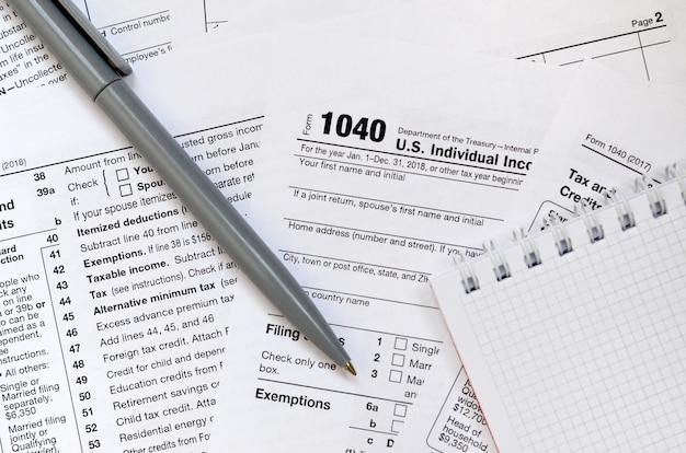 A caneta e o caderno encontram-se no formulário 1040 de imposto de renda individual dos eua. o tempo para pagar impostos Foto Premium
