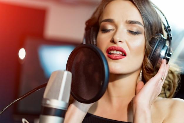A cantora bonita com fones de ouvido na frente do microfone canta com a boca aberta no estúdio moderno. Foto Premium