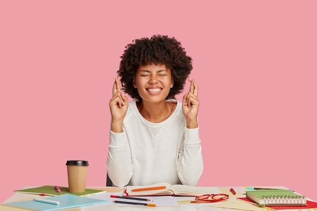 A cientista sorridente de pele escura mantém os dedos cruzados, posa na mesa e espera uma pesquisa bem-sucedida Foto gratuita
