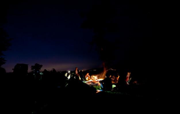 A companhia de jovens está sentada ao redor da fogueira e cantando canções Foto Premium