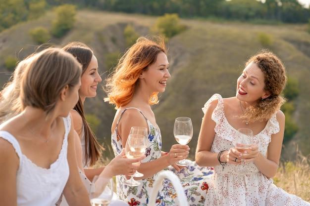 A companhia de lindas amigas se divertindo, bebendo vinho e desfrutando de um piquenique nas montanhas Foto Premium