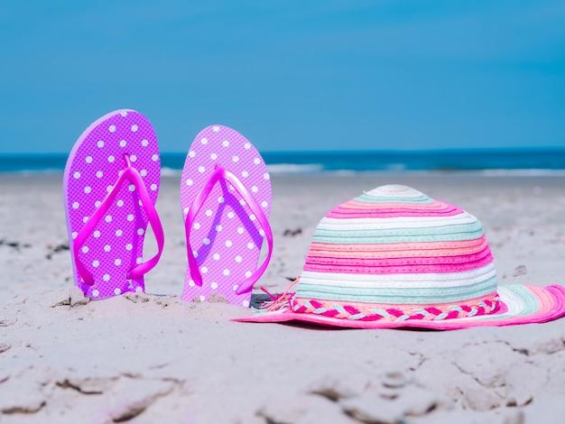A composição do verão com cccessories da praia encalha chinelos e chapéu colorido na areia tropical contra a parede azul do mar e do céu. conceito de férias de verão de férias na praia, passeio no mar, verão ensolarado quente. Foto Premium