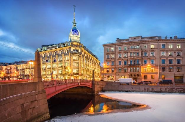 A construção da loja esders e scheyfals em são petersburgo à luz da iluminação noturna de inverno legenda: loja na ponte vermelha, esders e schefals Foto Premium