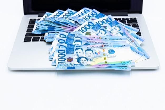 A conta filipino do peso com laptop, moeda do dinheiro de filipinas, contas de dinheiro filipinos, conceito faz o dinheiro do peso com laptop. Foto Premium
