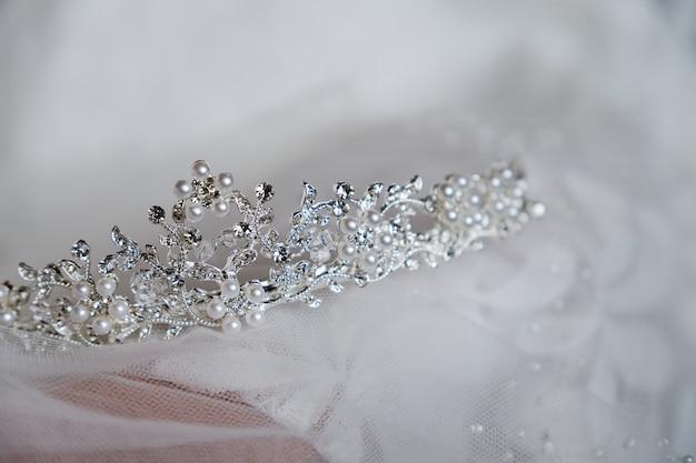 A coroa da noiva bonita está no véu, close-up. dia do casamento. noiva de manhã. Foto Premium