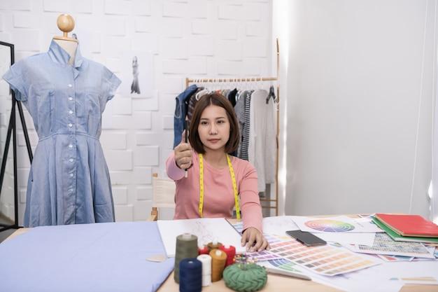 A costureira está projetando um vestido de noite no quarto. o alfaiate está trabalhando no seu melhor. Foto Premium