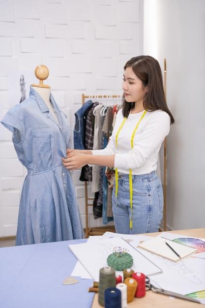 A costureira está projetando um vestido de noite no quarto. Foto Premium