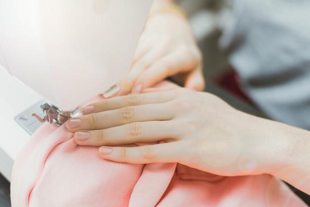 A costureira trabalha em uma máquina de costura. a menina costura e segura um pano rosa Foto Premium