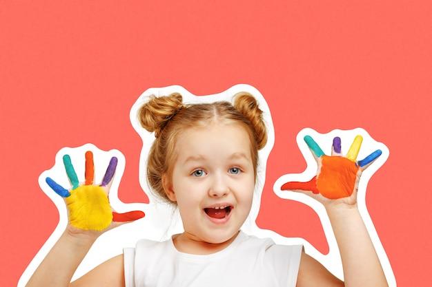 A criança alegre da menina mostra as mãos pintadas com pintura. Foto Premium