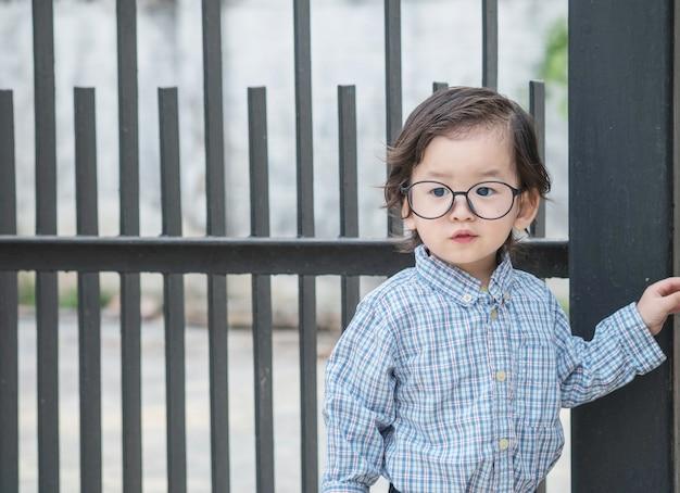 A criança asiática do close up com óculos está na frente do fundo textured da cerca de aço Foto Premium