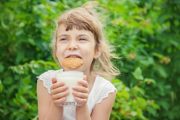 A criança bebe leite e biscoitos. foco seletivo. Foto Premium