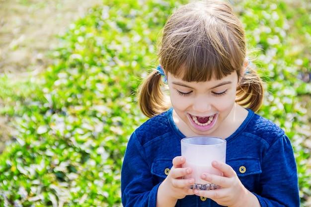 A criança bebe leite. foco seletivo. crianças. Foto Premium