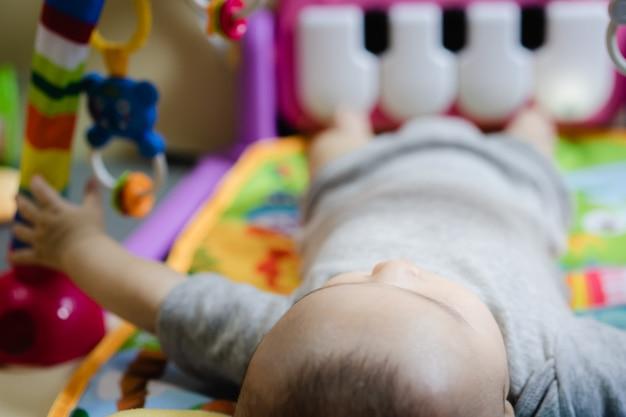 A criança brincando com boneca de plástico colorido Foto Premium