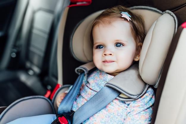 A criança consideravelmente pequena, menina com olhos azuis senta-se na poltrona do automóvel, prendida por cintos de segurança. Foto Premium