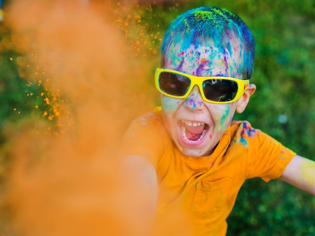 A criança de óculos lança tinta holi Foto Premium