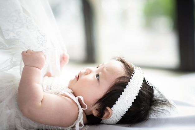 A criança de vestido branco está puxando o cobertor branco. Foto Premium