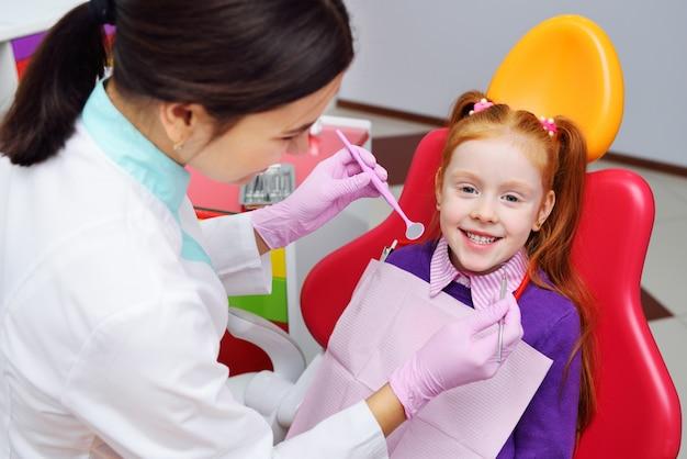 A criança é uma garotinha ruiva sorrindo sentado em uma cadeira odontológica. odontopediatria, dentes de leite Foto Premium