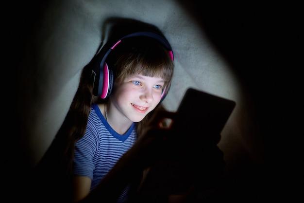 A criança em fones de ouvido sem fio ouve música à noite debaixo de um cobertor e olha para o tablet Foto Premium