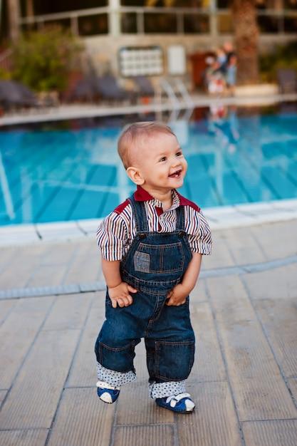 A criança em macacão jeans, ri e olha para longe, os primeiros passos Foto Premium
