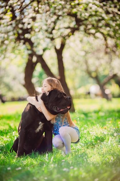 A criança encantadora abraçando um cachorro preto Foto gratuita