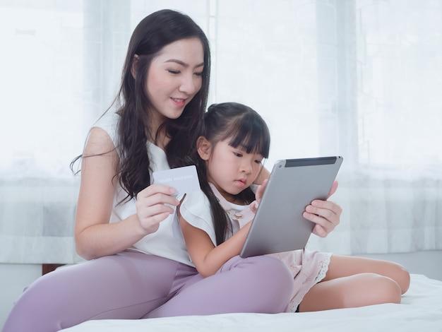A criança está brincando na cama com a mãe dela Foto Premium