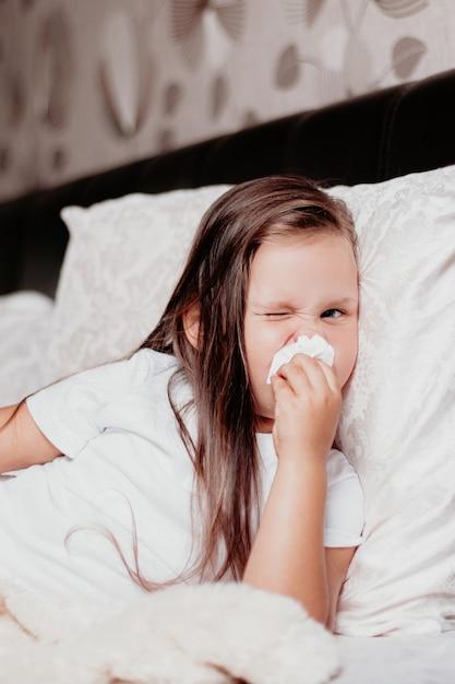 A criança está deitada com o nariz inchado e vermelho devido a coriza, um resfriado e uma segunda onda do vírus. Foto Premium