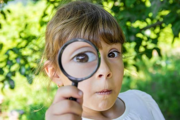 A criança está olhando em uma lupa. aumentar. foco seletivo. Foto Premium