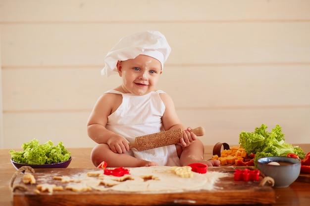 A criança pequena se senta na mesa perto de massa e legumes Foto gratuita