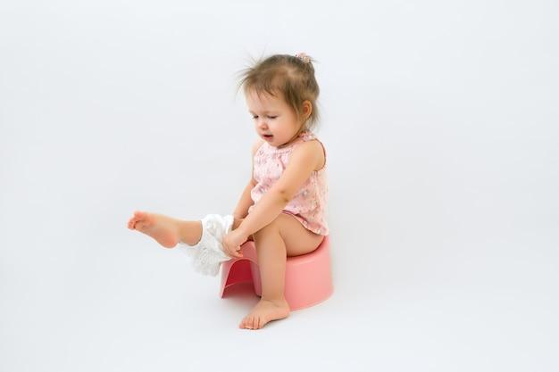 A criança senta no penico e veste a calcinha. Foto Premium
