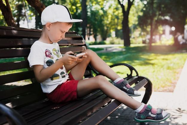 A criança senta-se no parque em um banco com um gadget. as crianças usam gadgets. retrato de um menino bonito no sol poente. um menino joga um jogo em um telefone celular. Foto Premium