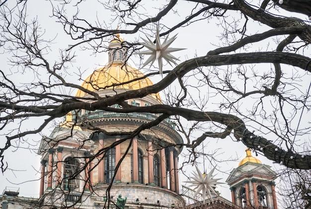 A cúpula da catedral de santo isaac em são petersburgo através de galhos de árvores e decorações de natal em forma de estrelas sob o céu de inverno Foto Premium