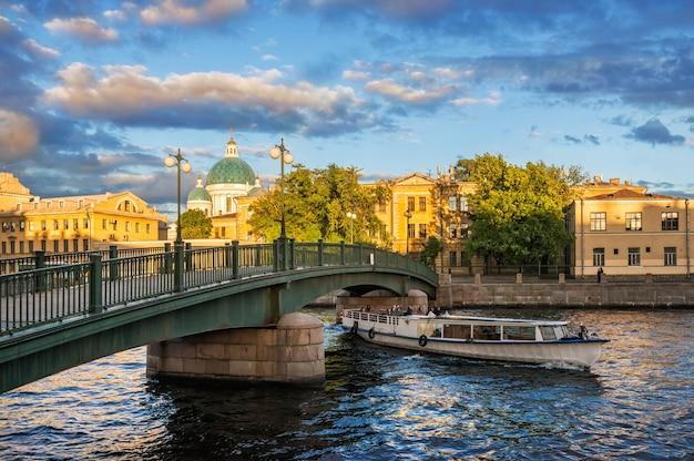 A cúpula da catedral izmaylovskiy e o navio de recreio navegam sob a ponte krasnoarmeysky sobre o rio fontanka em são petersburgo em uma noite ensolarada de verão Foto Premium